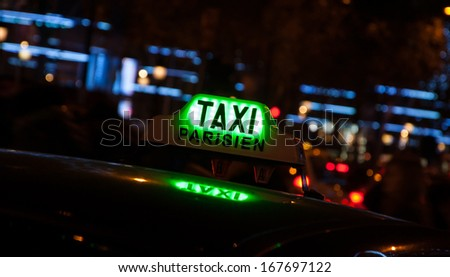 A Parisian taxi for hire at Avenue des Champs-Elysees decorated with Christmas illumination. - stock photo