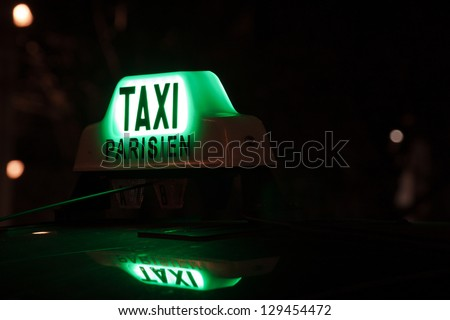 A Parisian taxi for hire in the centre of town. Green. - stock photo