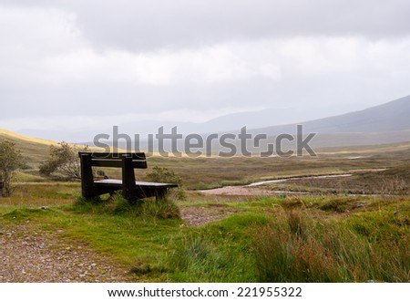 a park bench overlooking glencoe, scotland - stock photo
