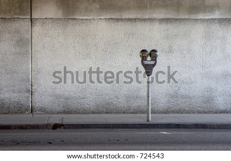 A parking meter under a freeway overpass. - stock photo