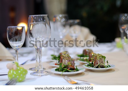A part of elegant table setting in luxury restaurant. Close up of wineglasses and snack. - stock photo