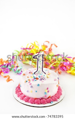 A party cake with one lit candle and party ribbons, selective focus, low key