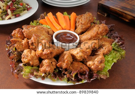 A party tray with chicken wings and carrot sticks - stock photo