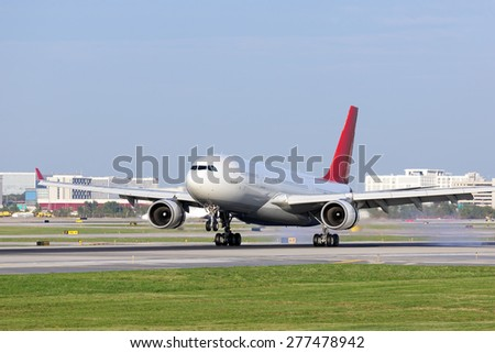 A passenger airplane touching down on the runway.  City buildings can be seen in the background. - stock photo