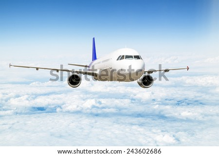 A passenger plane flying above the clouds in the sky at a height of ten thousand feet - stock photo
