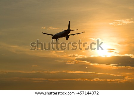 A passenger plane leaves in the evening sunset