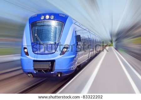 A passenger train travels at high speed through a train station with everything bar the train blurred out.