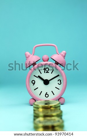 A pastel pink alarm clock placed in front  stacks of gold coins with pastel blue background, hence the phrase, time is money.