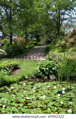 A path leading to a lily pond in a tranquil summer garden. - stock photo