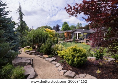 A path meanders between naturally sculptured small rocks, with a variety of trees and shrubs on either side. In the background, a beautiful contemporary home can be seen beyond a lush green lawn. - stock photo