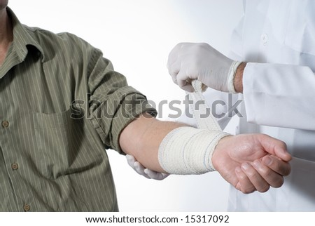 A patient is sitting in a wheelchair at a doctors office.  The doctor is bandaging his arm.  Horizontally framed shot. - stock photo