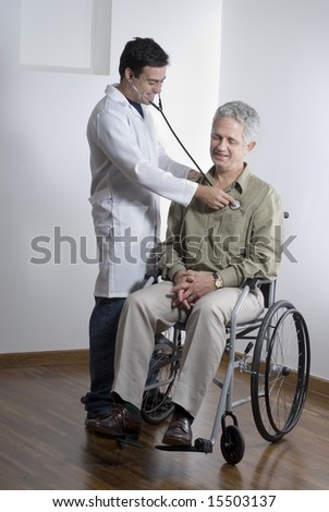 A patient is sitting in a wheelchair at a doctors office.  The doctor is listening to his heartbeat.  They are smiling and looking away from the camera.  Vertically framed shot.