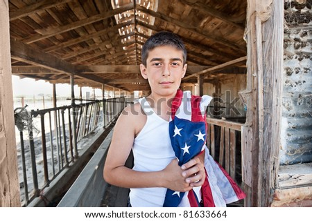 A patriotic teenager standing in the doorway of an old abandoned barn while holding an American flag. - stock photo