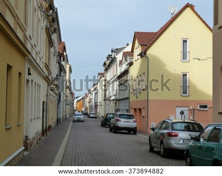 a paved road with houses and parked cars