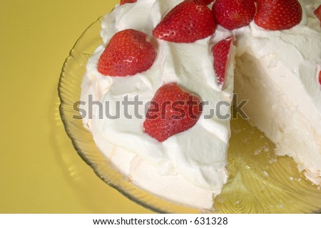 A pavlova dessert with a slice cut from it - stock photo