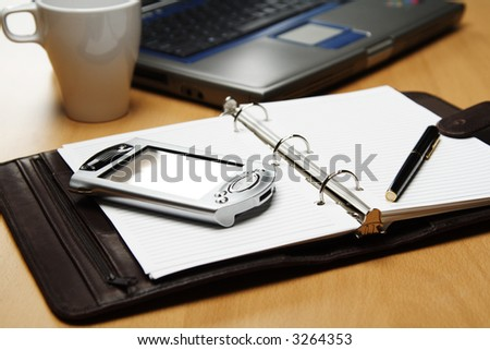 A PDA and a laptop for planning at the office - stock photo