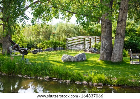 A peaceful green park with empty benches by a pond and wood brench - stock photo