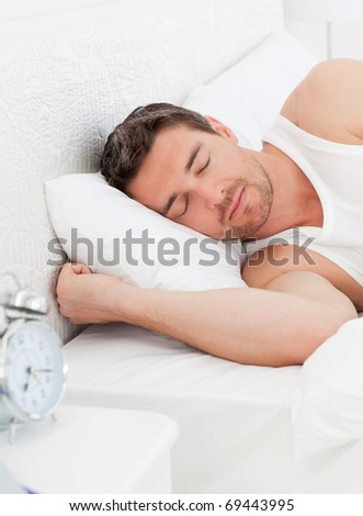 A peaceful man in his bed before waking up in his bedroom - stock photo