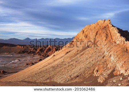 A peak in moon valley in the atacama desert (driest desert on earth) is bathed in the light of the setting sun in front of a stormy sky