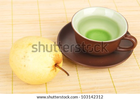 A pear with tea on mat
