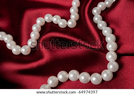 A pearl necklace on red satin