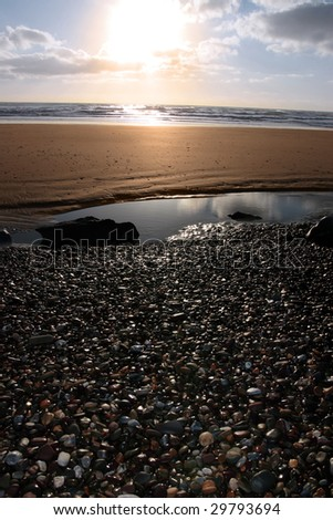 a pebble beach near ballybunion in county kerry ireland at sunset - stock photo