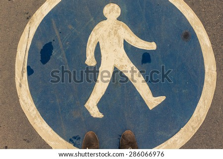 A pedestrian crossing sign on the pavement. - stock photo