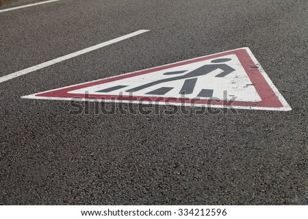 a pedestrian crossing sign on the pavement - stock photo