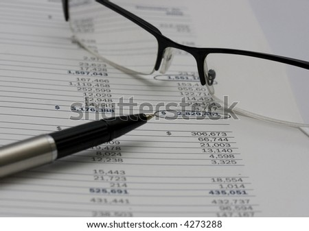 A pen and reading glasses resting on a financial report