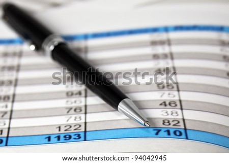 A pen lays on some Financial Analysis data report. Close-up - stock photo