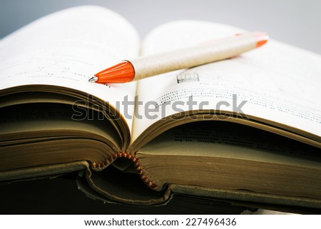 a pen on opened old textbook - stock photo
