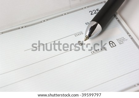 A pen resting on a blank check. - stock photo