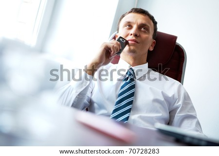 A pensive businessman sitting at table with a mobile phone - stock photo