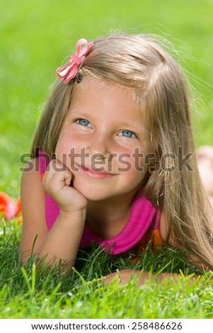 A pensive little girl is lying on the green grass in a summer day - stock photo