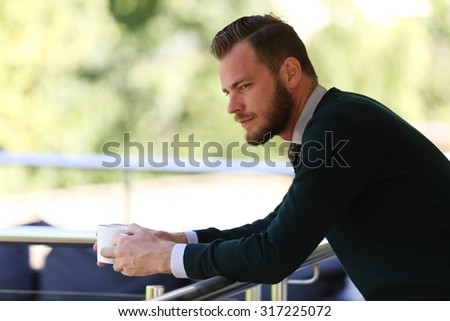 A pensive man wearing a pullover and holding a coffe mug, standing on a patio on a sunny summer day. - stock photo