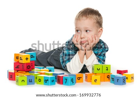 A pensive preschool boy is playing with blocks on the floor - stock photo