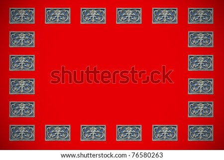 A peranakan floral timber carving border frame on a red painted wooden panel with blank space for copyspace text. - stock photo