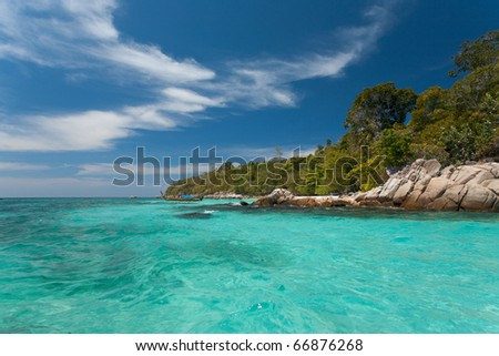 A perfect day with blue skies in paradise as the crystal clear turquoise ocean of the Andaman sea meets the edge of the destination holiday island of Ko Lipe, Thailand - stock photo