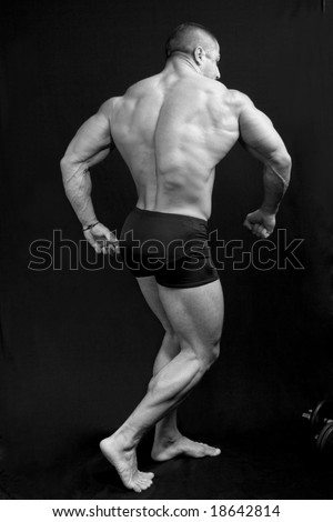 A perfect muscular man posing artistic, back double biceps - stock photo