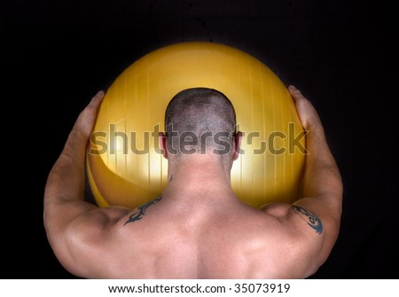 A perfect muscular man with yellow ball posing artistic,studio shot - stock photo