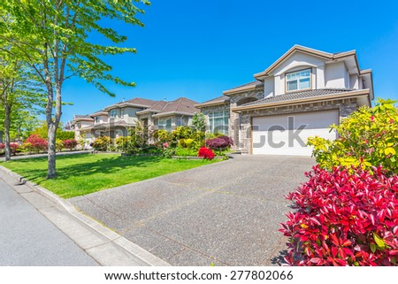 A perfect neighborhood on a sunny day with blue sky. Houses and townhouses in suburbs at Spring in the north America.