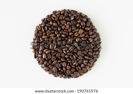 A perfectly round circular heap of coffee beans isolated against a white background. - stock photo