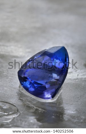 A perperfect cut of Tanzanite isolated on grey ice background. - stock photo