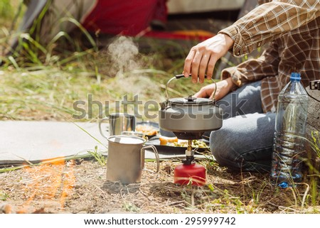 A person boiling water in a pot over a propane stove to make tea - stock photo