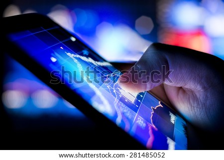 A person checking stock market data on a mobile device. - stock photo
