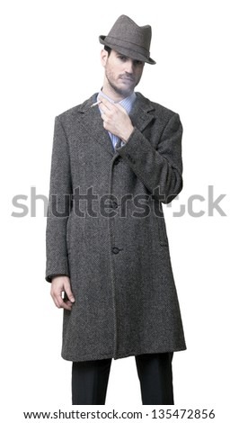 A person dressed in a gray overcoat and a gray hat. Holding a cigarette in his left hand, blowing smoke and looking at the camera with a confident expression. Isolated on white background. - stock photo