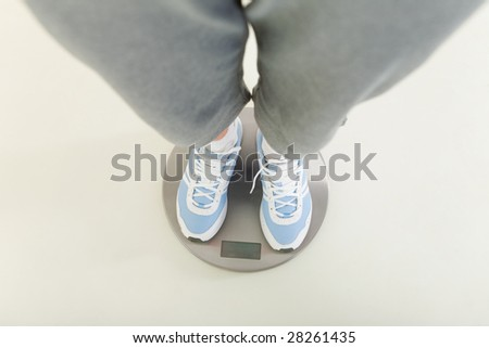 A person dressed sportswear standing on bathroom scales. View on legs. - stock photo