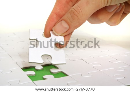 A person fullfilling a puzzle game by inserting the last piece. - stock photo