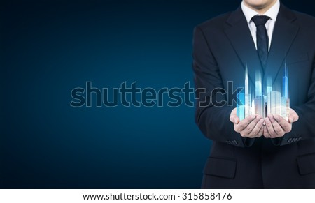 A person holds a hologram of skyscrapers as a symbol of financial success. - stock photo