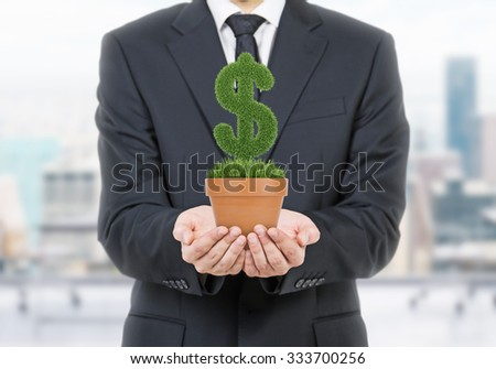 A person in formal suit holds a flowerpot with grass green dollar sign. Office open space in blur on the background. - stock photo